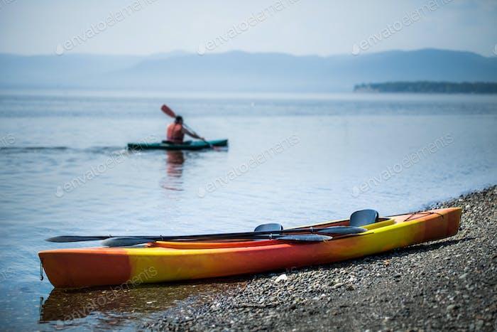 Kajak am Meer mit Kajakern im Hintergrund