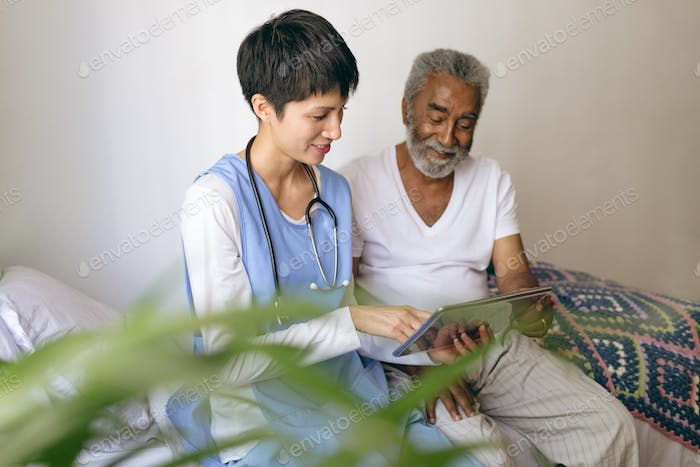 Female doctor and senior male patient using digital tablet at retirement home