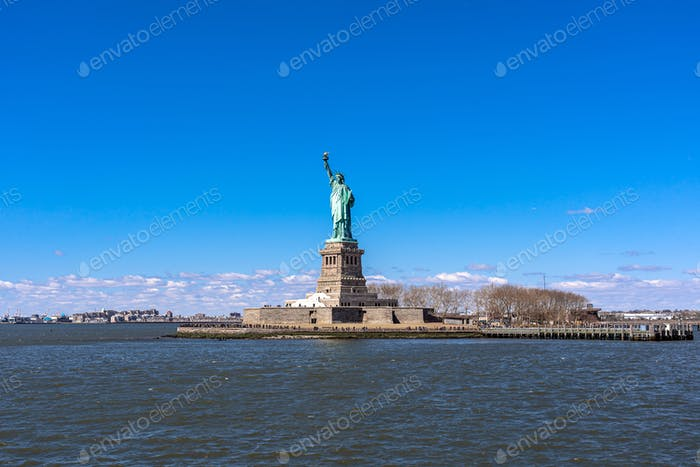 The Statue of Liberty under the blue sky background, Lower Manhattan, New York City