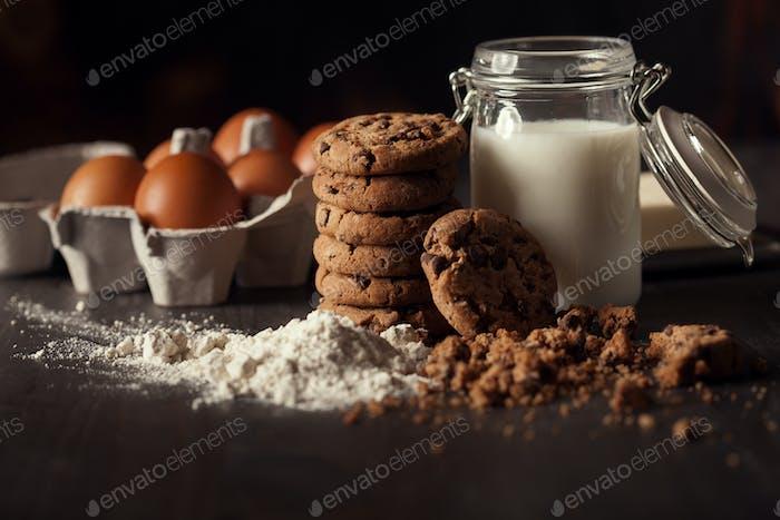 Schokoladenplätzchen auf rustikalem Holztisch mit einer Flasche Milch, Weißmehl, frischen Eiern, Butter und