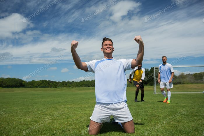 Excited football player in celebrating scoring goal kneeling on grass pitch