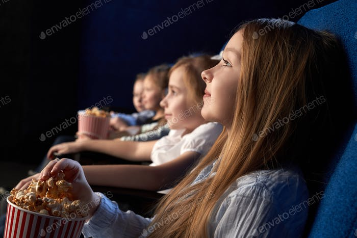 Children watching movie in cinema theatre