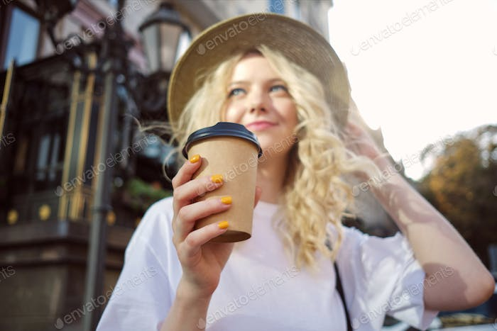 Fuzzy attractive casual blond girl in hat dreamily looking away with coffee to go on city street