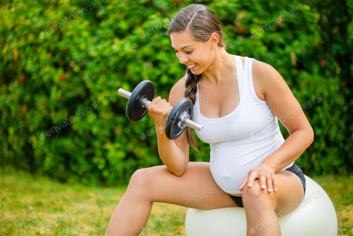 Healthy Pregnant Woman Lifting Weights On Exercise Ball In Park