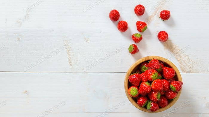 Red strawberries laying on white table from above with copy space
