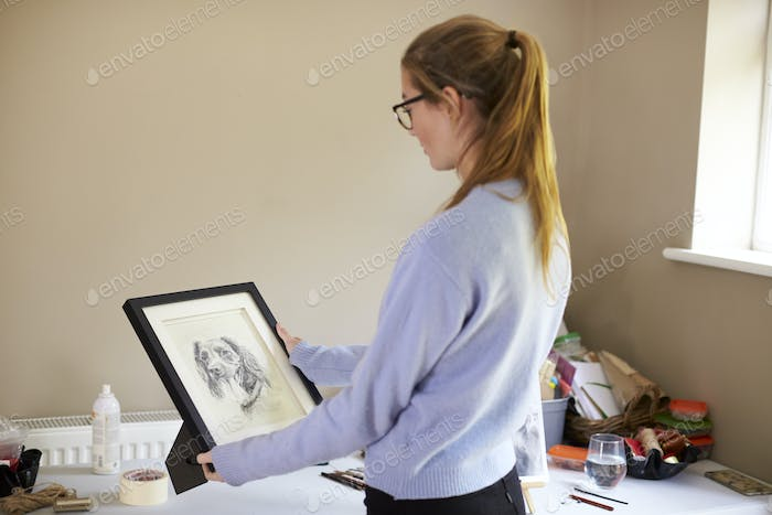 Female Teenage Artist Holding Framed Charcoal Drawing Of Dog In Studio