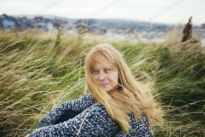 Portrait of blond woman sitting on grassy field