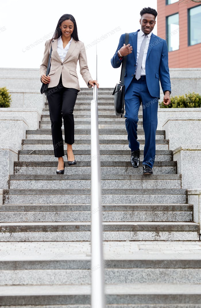 Businessman And Businesswoman Commuting To Work Walking Down Steps Outside Office Building
