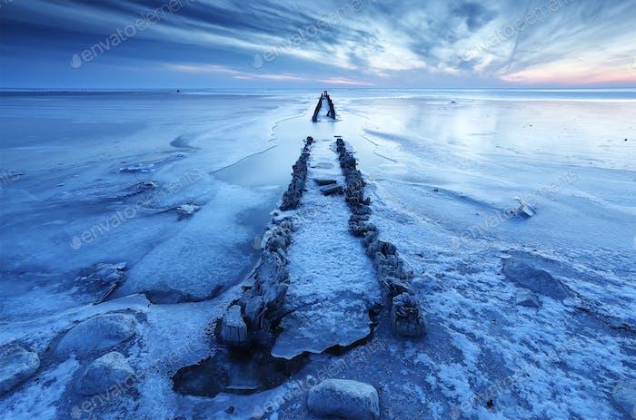 alte hölzerne Wellenbrecher im gefrorenen See während der Morgendämmerung