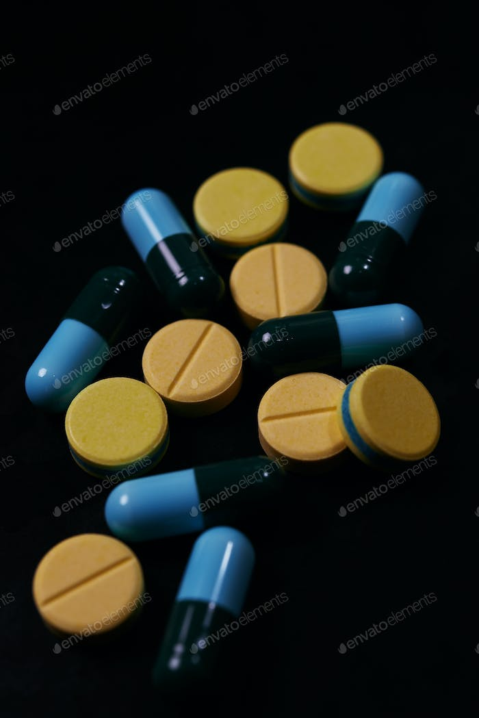 Pill and drug on black background