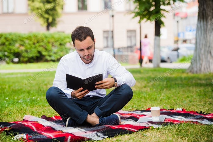 handsome young businessman reading book lying in the park