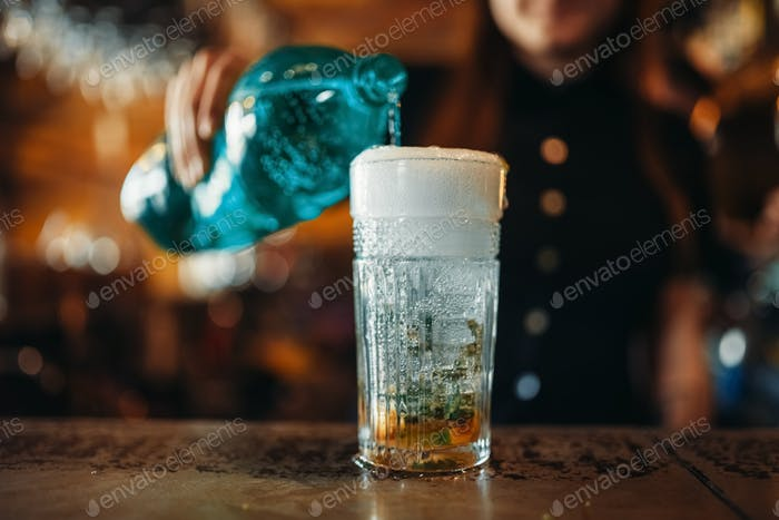 Female barman pours aerated water into a glass