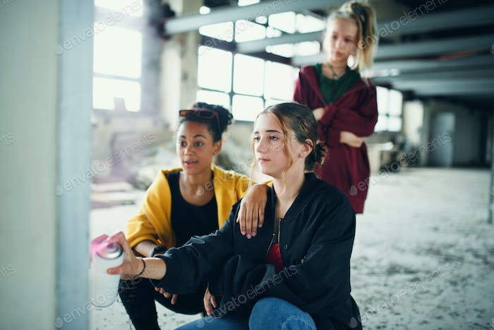 Group of teenagers girl gang indoors in abandoned building, using spray paint on wall