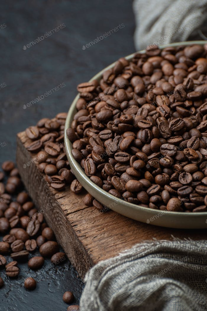 Coffee beans in a plate on a wooden stand. Close-up photography