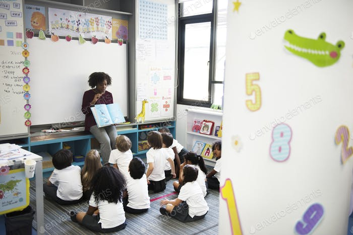 Kindergarten students sitting on the floor listening to story te