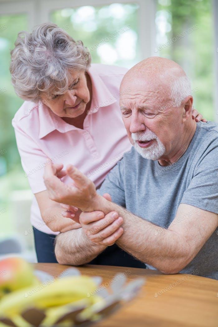 Ältere Frau steht neben ihrem älteren Mann, der das Handgelenk hält