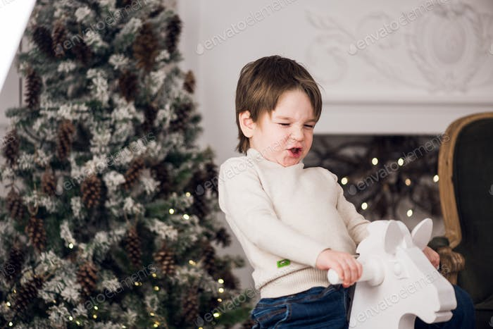 little boy riding horse in a christmas interior