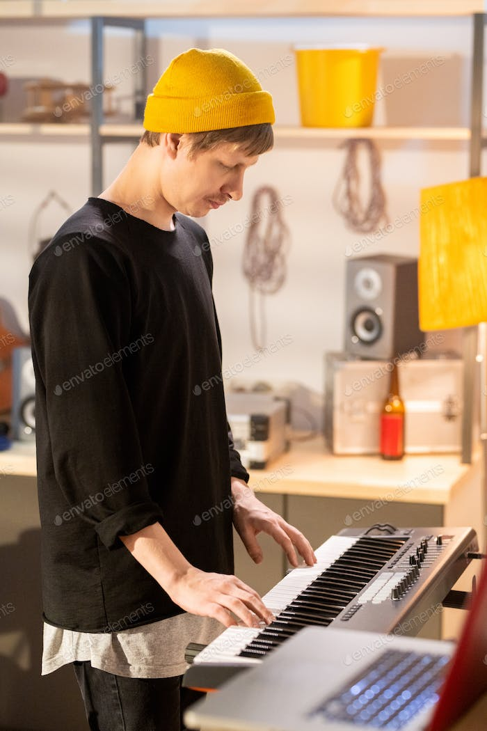 Side view of young musician touching keys of pianoboard while recording music