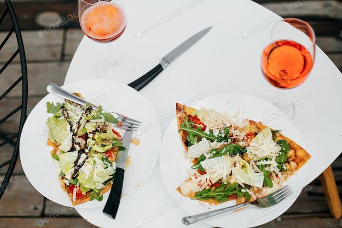 Hausgemachte Pizza und Aperol Drink auf modernen weißen Tisch