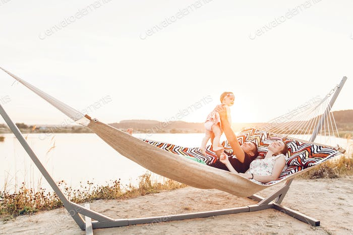 Smiling father and mother holding cute little girl while lying in a hammock