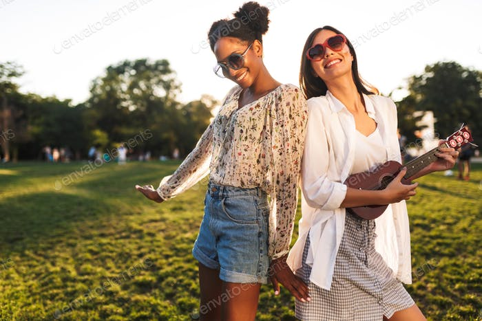 Joyful girls in sunglasses happily playing on little guitar and