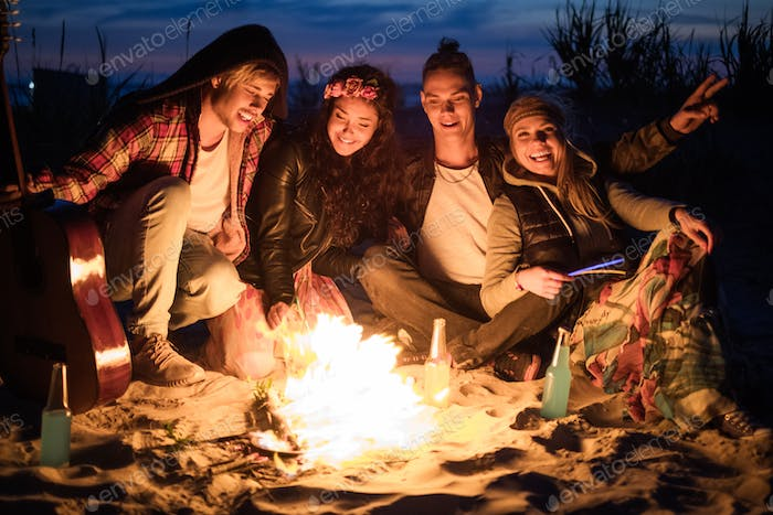 Hippie friends with guitar near bonfire