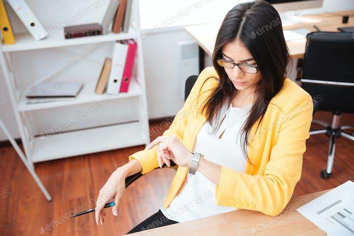 Businesswoman looking on wrist watch in office