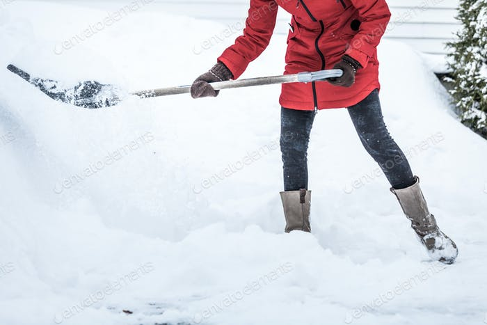 Close-up of Woman Shoveling her Parking lot