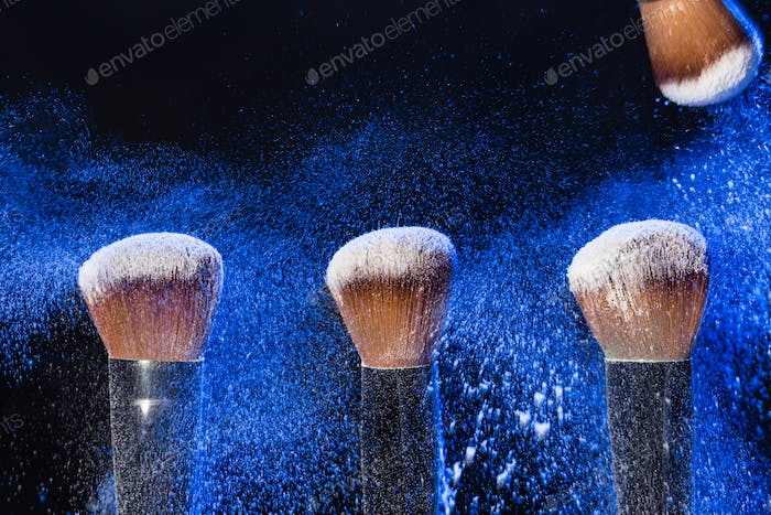 Make up, beauty and mineral powder concept - brush with blue powder on black background
