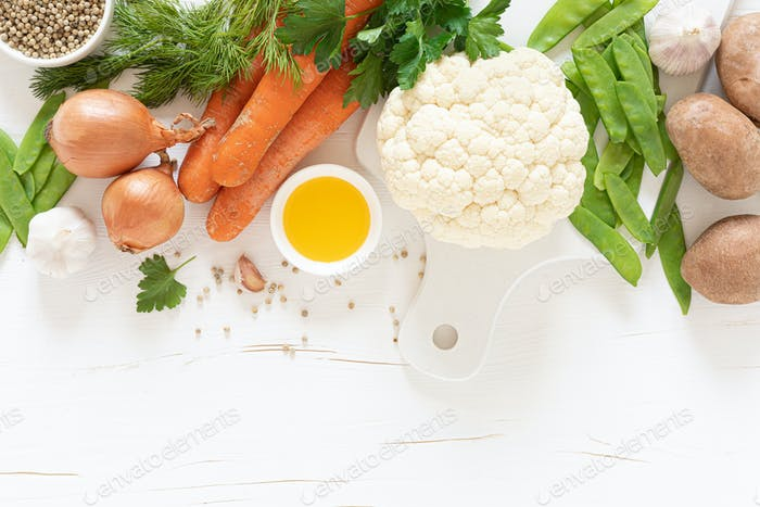 Fresh raw vegetables on white kitchen table, culinary background, top view