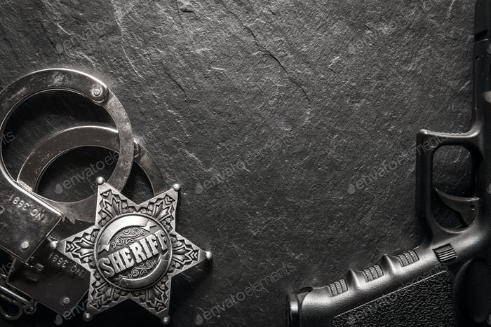 Sheriff star and handcuffs on black slate table