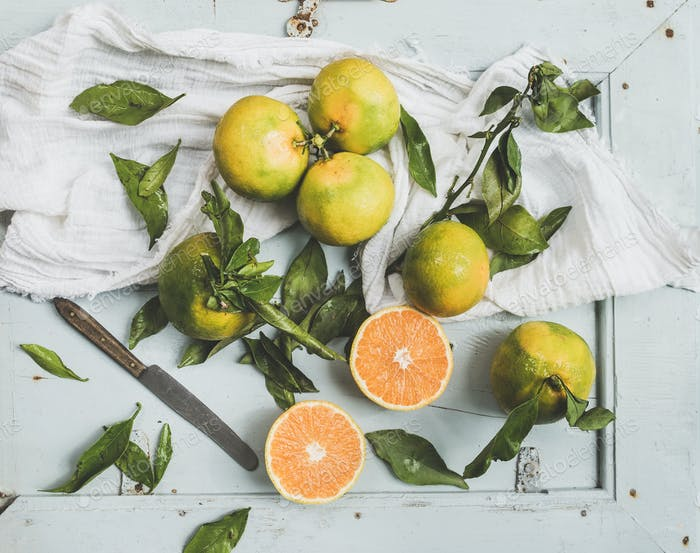 Fresh Turkish tangerines with leaves over blue rustic wooden backdrop