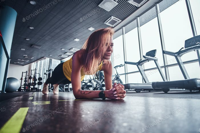 Slim fitness woman working in the modern gym, doing the plank on a mat