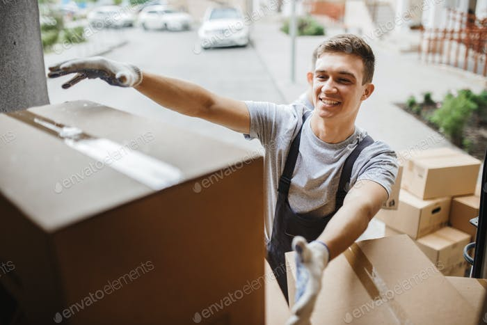 A young handsome smiling mover wearing uniform is reaching for the box while unloading the van full
