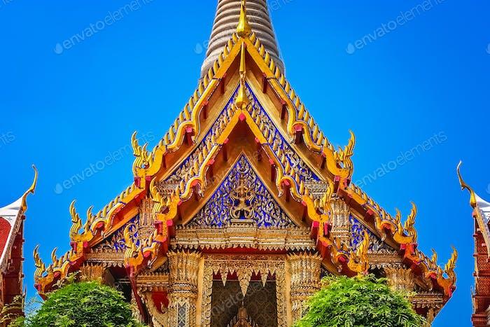 Verziertes goldenes dreieckiges Dach eines buddhistischen Tempels
