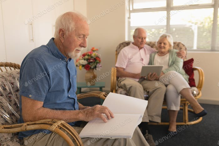 Senior man reading a braille book while senior couple using digital tablet at nursing home