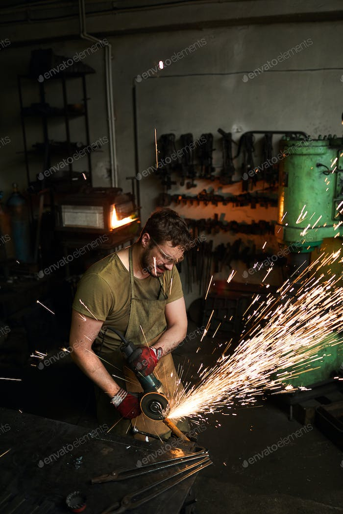 Busy strong blacksmith grinding metal