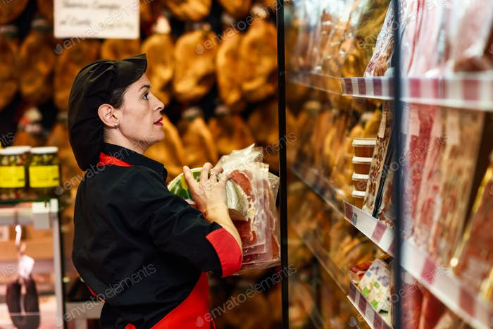 Portrait of female worker taking products in butcher shop