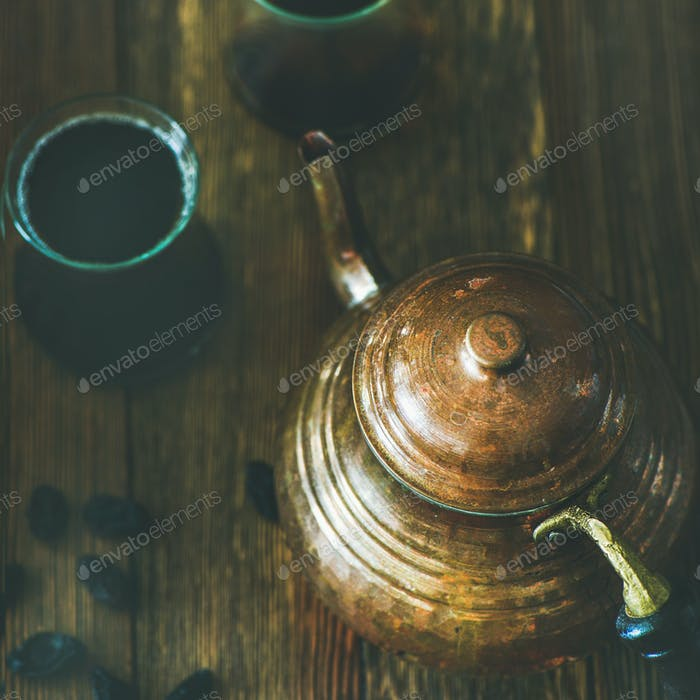 Oriental teapot, black tea in glasses and raisins, square crop