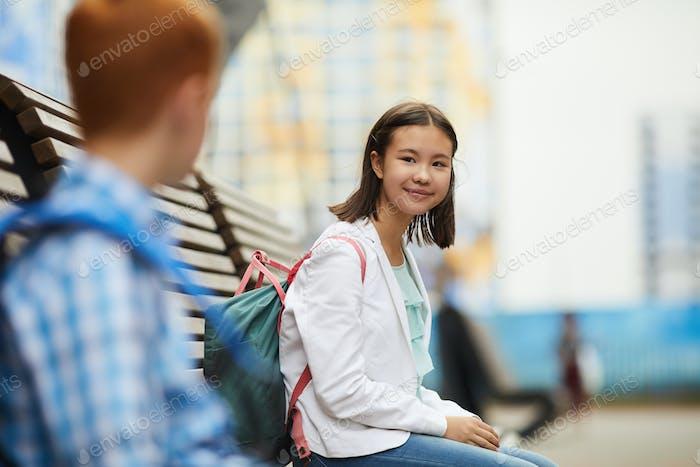 Schulmädchen im Gespräch mit ihrem Klassenkameraden