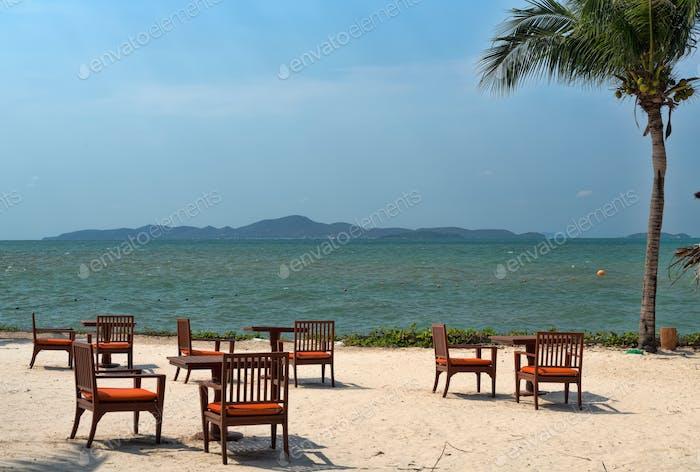 Tische am Strand mit Palme