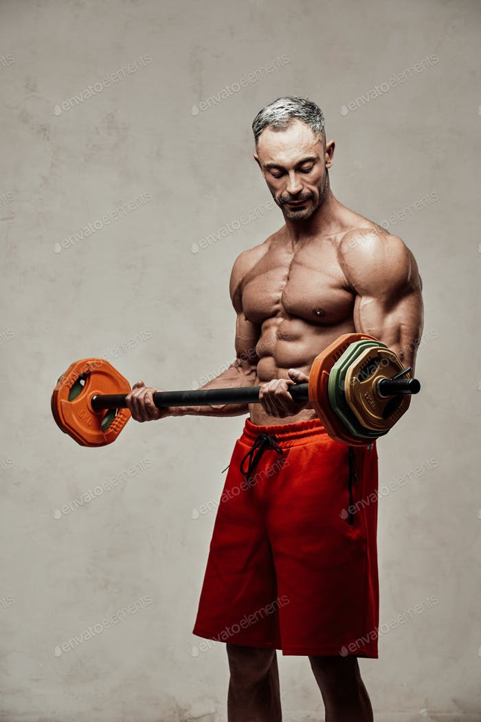 Handsome adult sportsman wearing sportswear posing for a camera while holding a barbell