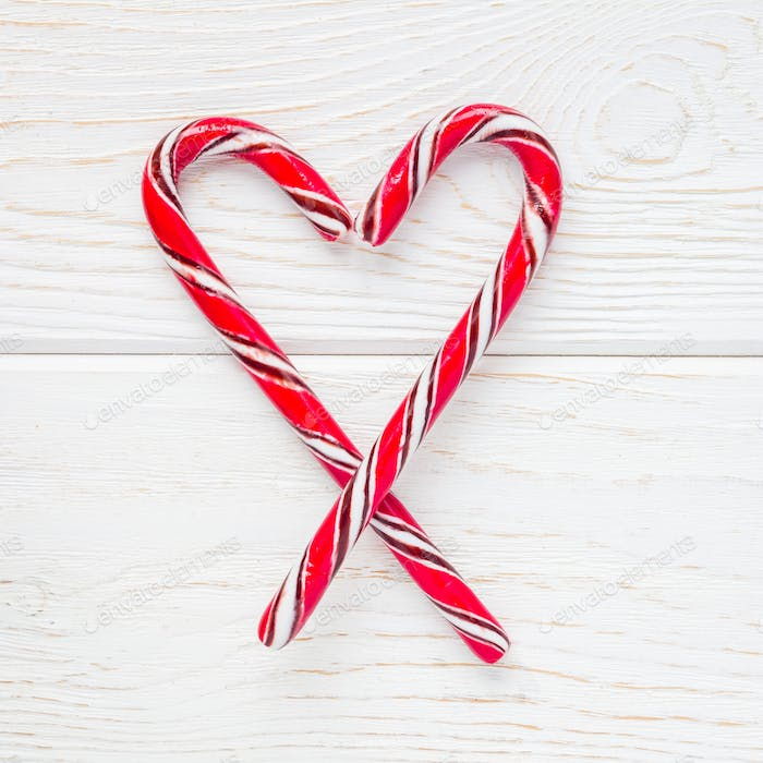 Crossed peppermint candy canes on a white wooden background, top view, square format