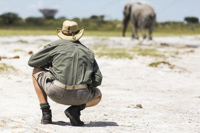 A guide crouching close to an elephant in Nxai Pan, Botswana