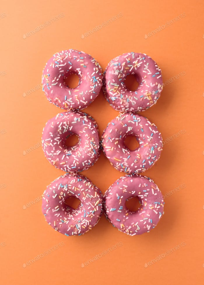 decorated pink donuts on color background