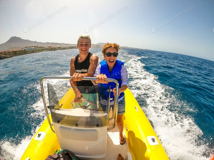 mom and son having fun and enjoying together in a boat driving it and discovering the sea smiling