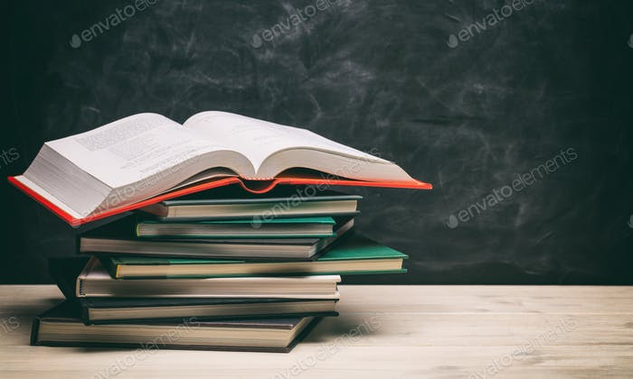 Books stacks on blackboard background