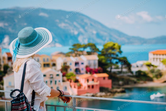 Tourist woman wearing blue sunhat and white clothes enjoying view of colorful tranquil village Assos