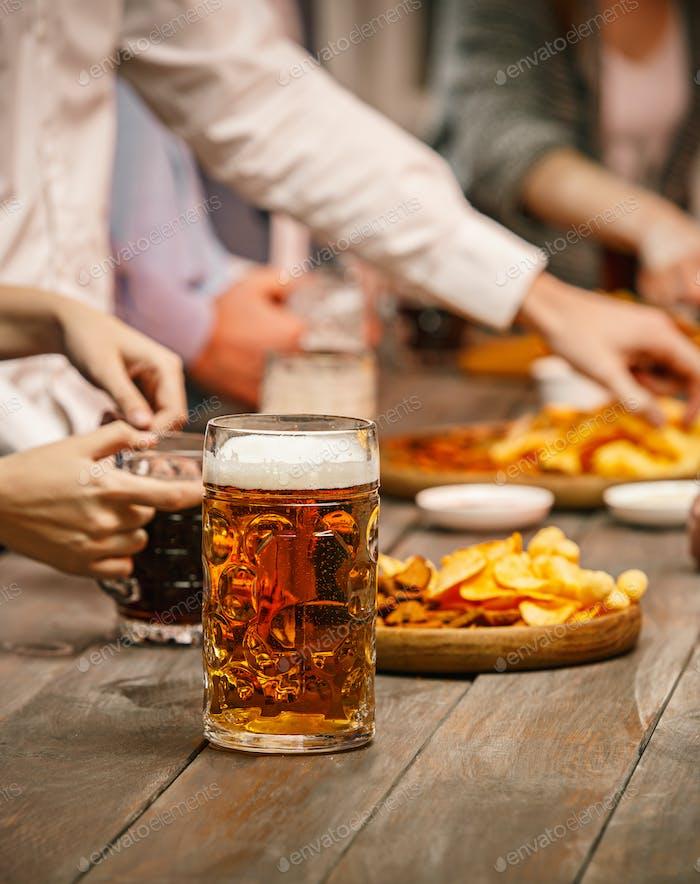 Gruppe von Freunden genießen abendliche Getränke mit Bier