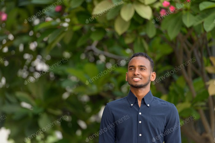 Handsome African businessman outdoors at rooftop garden thinking